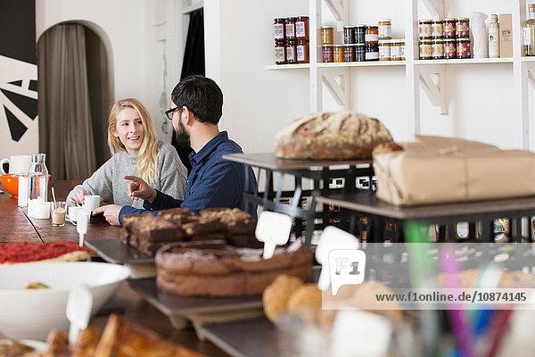 Kundenpaar sitzt am Café-Tisch und unterhält sich