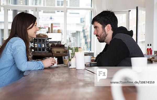 Mittelgroßes erwachsenes Paar sitzt am Café-Tisch bei Kaffee und unterhält sich
