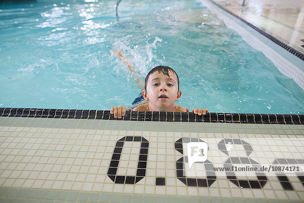Boy hanging onto edge at shallow end of pool