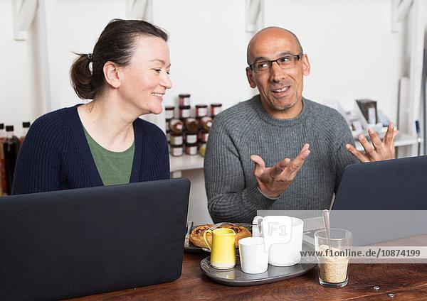 Ehepaar sitzt mit Laptop am Café-Tisch