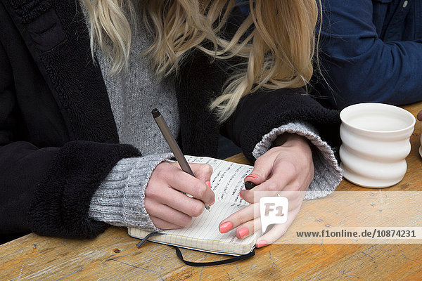 Hand of woman at cafe table writing in note book