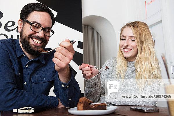 Glückliches Paar isst Schokoladen-Brownies am Kaffeetisch Glückliches Paar isst Schokoladen-Brownies am Kaffeetisch