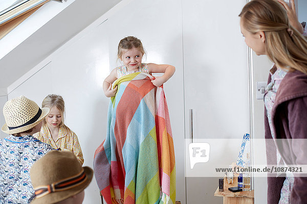 Mutter und Kinder beim Ankleiden im Dachgeschoss