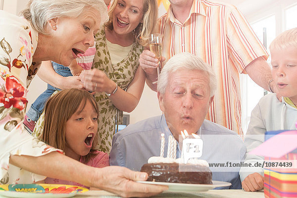 Man surrounded by family blowing out candle on birthday cake