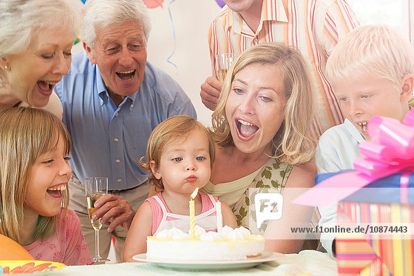 Baby girl surrounded by family blowing out candle on birthday cake