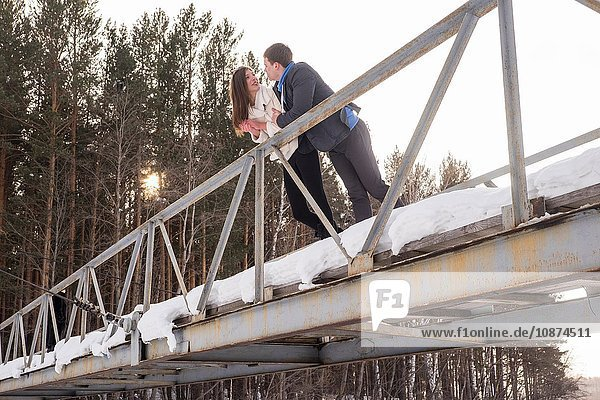 Young couple chatting  leaning on bridge railing
