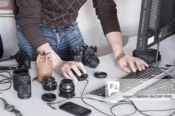 Fotograf  der Fotos von der Kamera in den Computer im Studio hochlädt