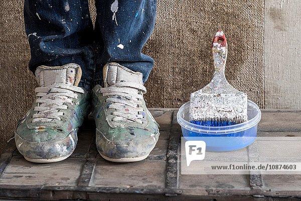 Beine mit schmutzigen Schuhen neben Plastikbehälter mit Pinsel