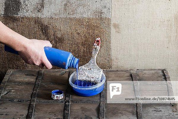 Farbe mit der Hand mit einem Pinsel in einen Kunststoffbehälter gießen