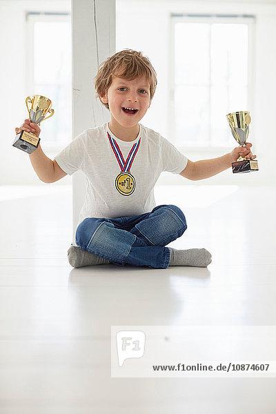 Porträt eines Jungen mit Goldmedaille  der Trophäen hochhält