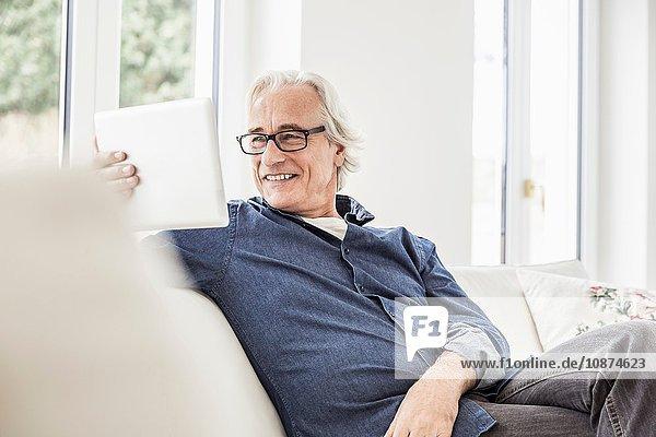 Älterer Mann sitzt auf dem Sofa und benutzt ein digitales Tablett
