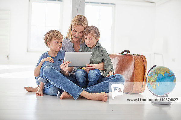 Mature woman and two son's sitting on floor looking at digital tablet together