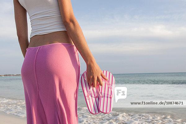 Schnappschuss einer Frau am Strand mit gestreiften rosa Flip-Flops in der Hand  Mallorca  Spanien