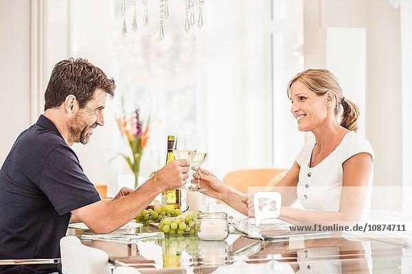Ein reifes Paar sitzt am Tisch  hält Weingläser und macht Toast