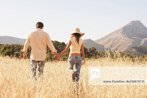 Rear view of couple strolling in field of long grass  Majorca  Spain