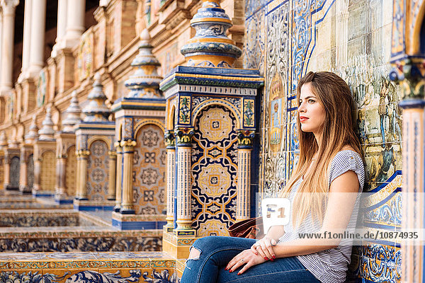 Portrait of young woman sitting relaxing at Plaza de Espana  Seville  Andalucia  Spain