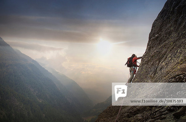 Climber on a rocky wall above a valley  Alps  Canton Bern  Switzerland