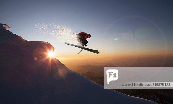 Skifahrer springt bei Sonnenuntergang auf einem verschneiten Hang  Zermatt  Kanton Wallis  Schweiz