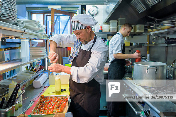 Chef preparing tomatoes in traditional Italian restaurant kitchen
