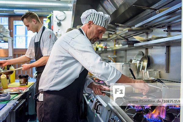 Chefs preparing food in traditional Italian restaurant kitchen
