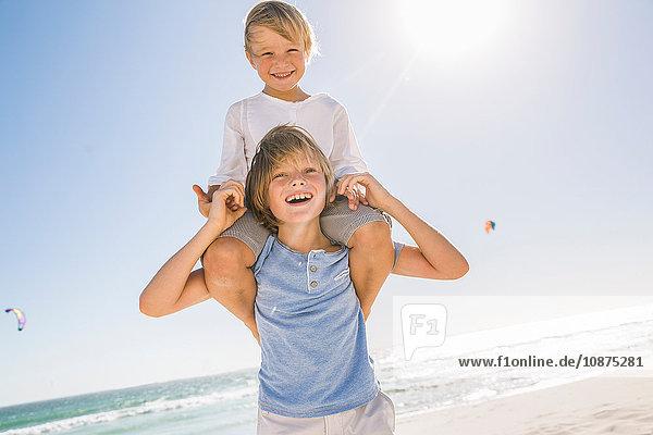 Großer Bruder am Strand trägt Junge lächelnd auf den Schultern