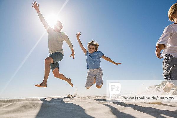 Vater und Söhne am Strand  mit erhobenen Armen in die Luft springend