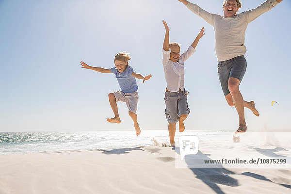 Father and sons on beach  arms raised jumping in mid air