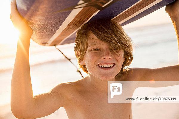 Junge trägt Surfbrett über Kopf lächelnd
