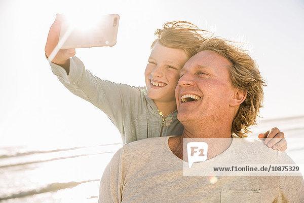 Sohn am Strand benutzt Smartphone  um sich selbst zum Lächeln zu bringen