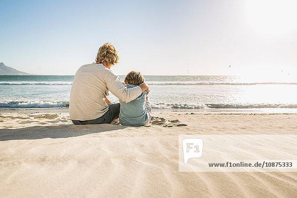 Vater und Sohn sitzen am Strand und schauen weg