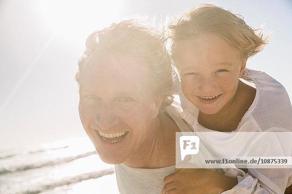 Vater am Strand gibt Sohn Huckepack und schaut lächelnd in die Kamera