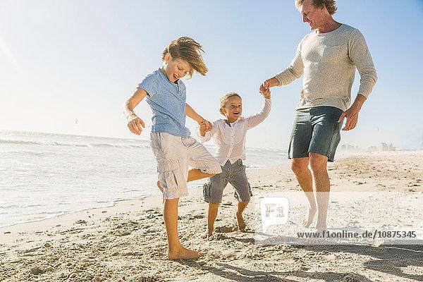 Vater und Söhne am Strand beim Händchenhalten