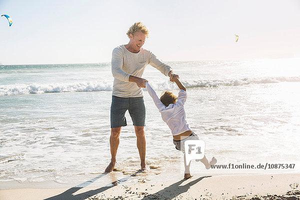 Vater und Sohn am Strand und halten sich beim Paddeln an den Händen