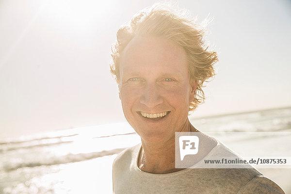 Porträt eines Mannes am Meer  der lächelnd in die Kamera schaut