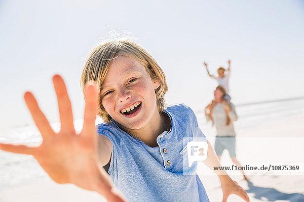 Junge am Strand schaut in die Kamera  die Hand erhoben lächelnd