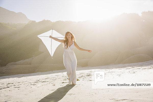 Frontansicht einer Frau am Strand in voller Länge  die ein weißes Kleid trägt und einen Drachen hält