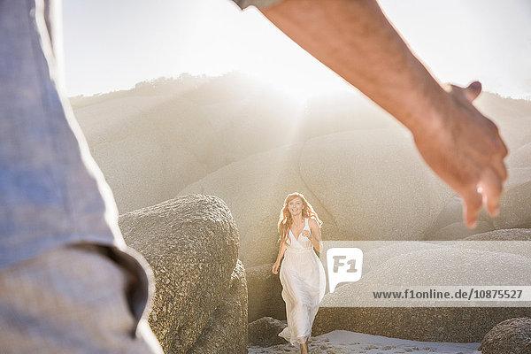 Blick durch Männerarme einer Frau in weißem Kleid  die zu ihm läuft
