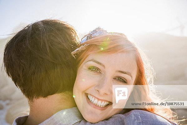 Blick über die Schulter einer Frau  die einen Mann umarmt und lächelnd in die Kamera schaut
