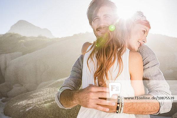 Mann umarmt rothaarige Frau vor Felsen lächelnd