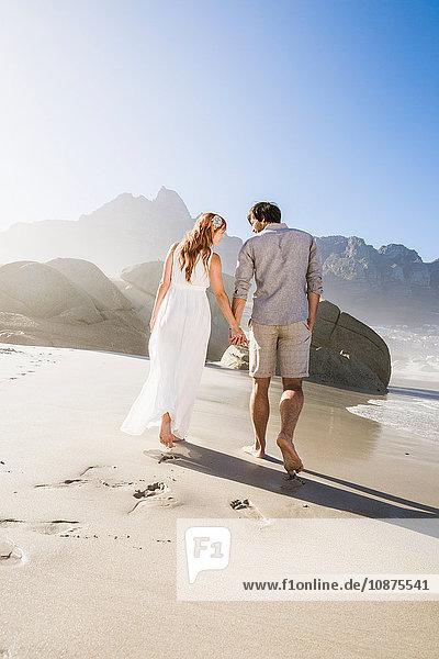 Rückansicht eines Paares  das am Strand spazieren geht und sich an den Händen hält  in voller Länge