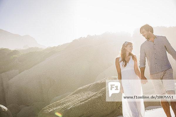 Paar vor Felsen  Hände haltend  Gesicht an Gesicht lächelnd