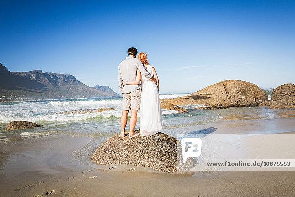 Rückansicht des Paares in voller Länge  die Arme umeinander gelegt  auf einem Felsen an der Küste stehend