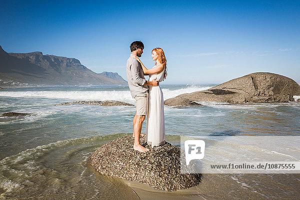 Ganzflächige Seitenansicht eines Mannes und einer Frau  die auf einem Felsen stehen  von Angesicht zu Angesicht