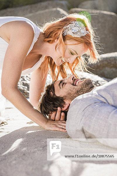 Kopf und Schultern eines am Strand liegenden Paares lächelnd von Angesicht zu Angesicht