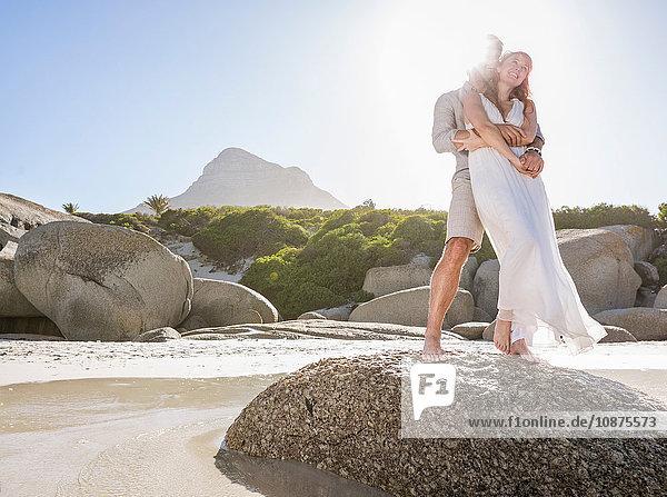 Ansicht in voller Länge eines auf Felsen stehenden Paares  das sich umarmt