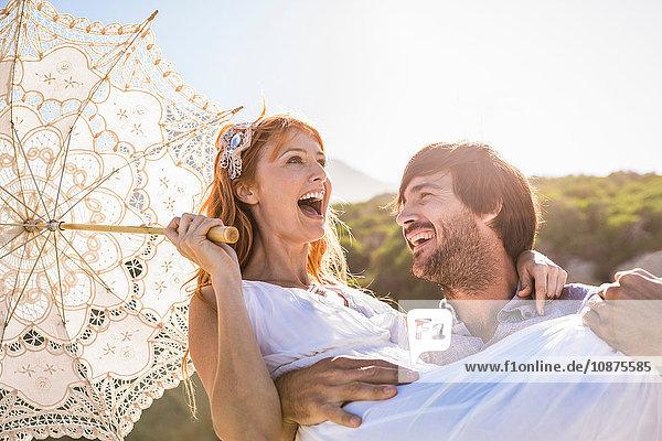Mann trägt Frau  die lächelnd einen Spitzenschirm in den Armen hält