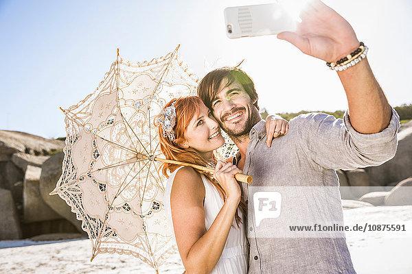 Pärchen am Strand mit Spitzenschirm und Smartphone zur Selbstbedienung