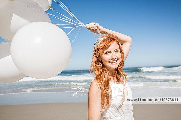 Rothaarige Frau am Strand hält Ballons und schaut lächelnd in die Kamera