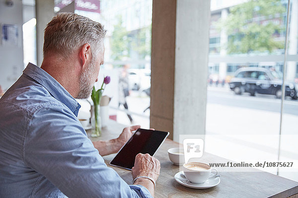 Älterer Mann sitzt im Café  benutzt digitales Tablett  Rückansicht