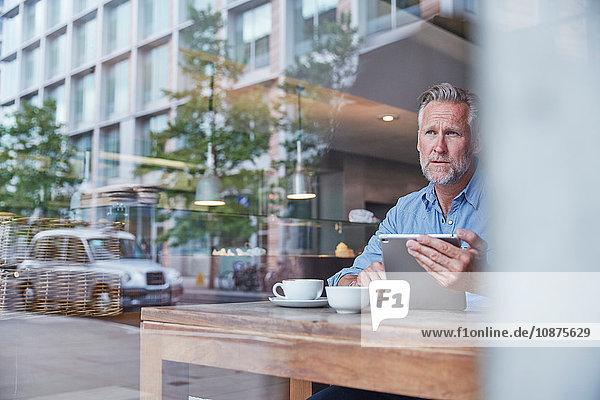 Reifer Mann sitzt im Café  benutzt digitales Tablett  Straße spiegelt sich im Fenster